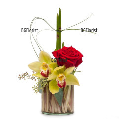 Красива аранжировка в стъклен съд от орхидеи и рози